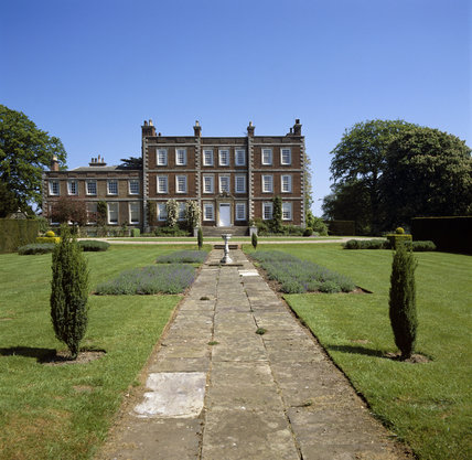 A view along the garden path to the entrance front of the red brick house which was built in 1700