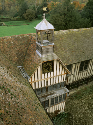 View of the low tower at Ightham Mote in Kent, with a one-handed clock, dated 1798 on the dial, and a bell above it, which strikes the hours