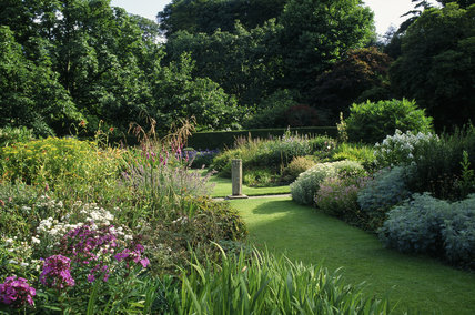 Grass pathway through the herbaceous border with a sundial in the garden at Lanhydrock