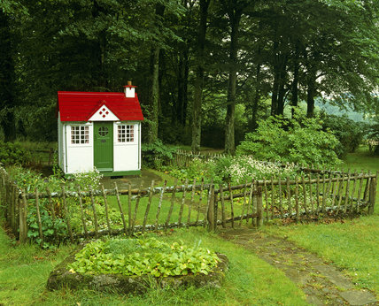 The Bunty House, in a secluded section of the gardens at Castle Drogo, surounded by trees and shrubs, the brightly painted playhouse stands out very well