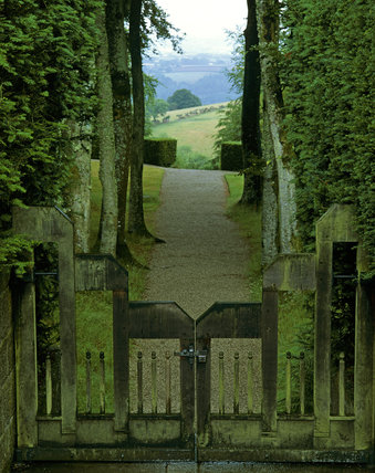 A wooden gate leading to a gravel path between tall trees with a view to rolling country beyond at Castle Drogo