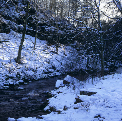 Hebden Water running through snow covered woods at Hardcastle Crags