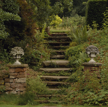 Acorn Bank, view up stone steps with ornamental urns, at Acorn Bank, Cumbria