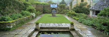 Courtyard garden at Snowshill with stone paving and glimpse of pond