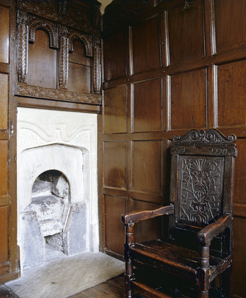 The Red Porch Chamber at East Riddlesden Hall, West Yorkshire - a partial view of the corner with a mid-17th century oak chair and fireplace