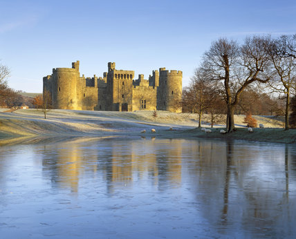 A wintry view of Bodiam Castle with a light dusting of snow on the ground