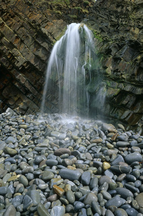 Waterfall and rock strata at Sandy Mouth with smooth wet pebbles in foreground