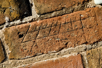 Graffitti sundial carved n the brickwork at The Workhouse, Southwell, Nottinghamshire, a C19th institution for paupers