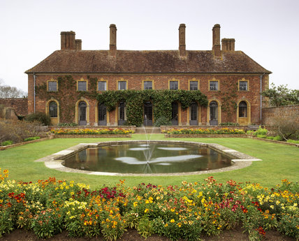 West aspect of Barrington court with Lily pond garden and Wallflowers, Cheiranthus 'Persian Carpet', April