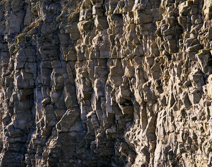 Close view of the limestone cliff at Dancing Ledge, a disused stone quarry on the Spyway Farm Estate, Purbeck, Dorset