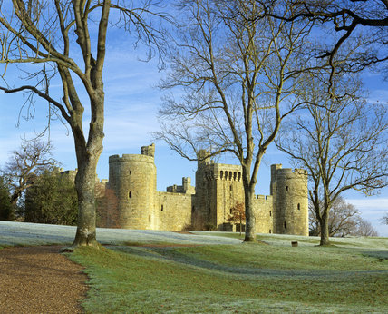 Exterior view of Bodiam Castle, near Robertsbridge, East Sussex,  in winter across frosty grass with trees