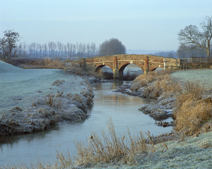 A view of the River Rother at Bodiam Castle, taken in February with frost covering the banks and the bridge that crosses it
