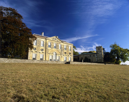 West front of Claydon house across grassland in late summer