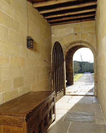 The stone-flagged Passage, looking towards the open door to the garden, at East Riddlesden Hall, West Yorkshire