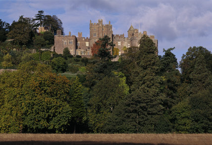 A general view of Dunster Castle from the south, with dense woodland in the foreground