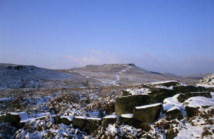 The Carl Wark, an Iron Age hill-fort, at Longshaw Estate in winter with snow-covered rocks in the foreground