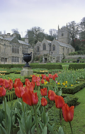 A view of the church across the garden with scarlet tulips in the foreground