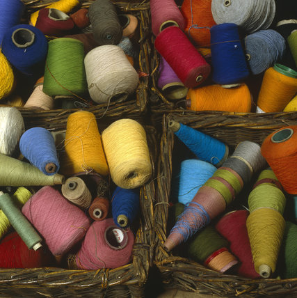 Colourful cotton reels in baskets
