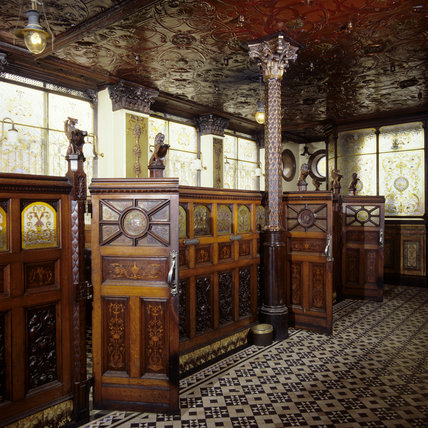 The snug stalls in The Crown with tiled floor and stained glass set into the wooden panels