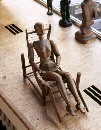 Wooden figure on a prototype chair model by Erno Goldfinger at 2 Willow Road, Hampstead, the house designed and built by Goldfinger in 1939