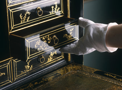 Gloved hand opening the drawer of the black lacquered secretaire
