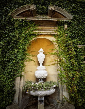 An urn set in an ornate niche surrounded by foliage, in the grounds of Belton House