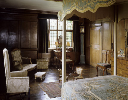 View of Queen Mary's Bedroom at Packwood House, showing the bed, wall panelling dating from Charles II's reign, dressing table and window