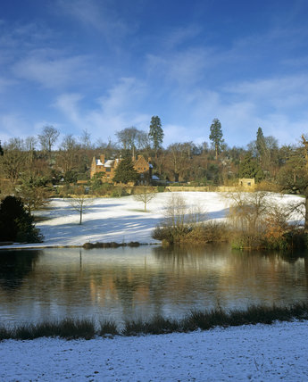 A view of Chartwell in winter with snow on the ground, with the upper lake in view in the foreground