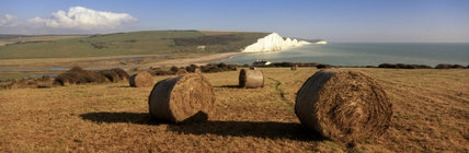 Close-up of bales of hay near Chyngton Farm, on the west bank of the River Cuckmere estuary, with the spectacular white Seven Sisters cliffs and calm turquoise sea beyond
