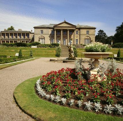 View of the south elevation of Tatton Park from the parterre, showing the colourful flower bed with urn and sculptural fountain