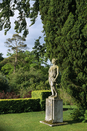 View of a statue of Diana on a plinth in the garden at Hinton Ampner in June