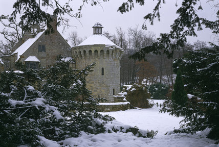 Scotney Castle in winter, with snow on the ground, roof tops and trees
