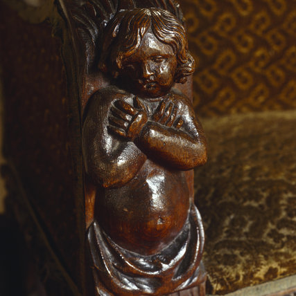 Close-up view of carved wooden cherub on arm of sofa in the Corridor at Oxburgh Hall