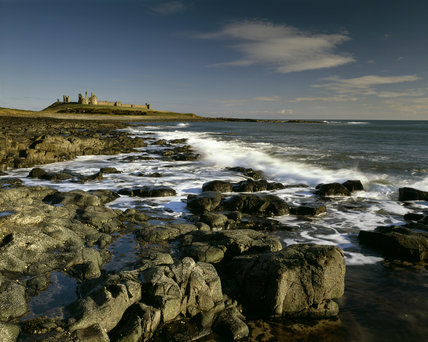 View of Dunstanburgh Castle from the south showing the incoming tide in early morning