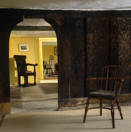 Detail of the original plank and muntin screen decorated with paintings from C15th in the Parlour, looking through to the Hall at Marker's Cottage