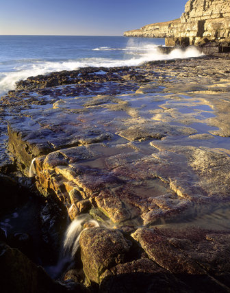 View of sea spray on the wave cut platform below Seacombe Cliff in Purbeck, Dorset, part of the Eastington Farm Estate