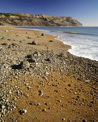 View of the pebble and shingle beach at Ringstead Bay in Dorset with the headland of White Nothe in the distance