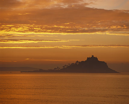 St.Michael's Mount silhouetted against a dramatic dawn sky.