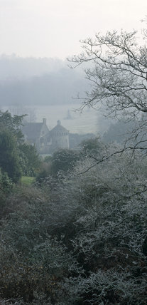 Looking down at the castle at Scotney Castle Garden through frost covered trees and plants