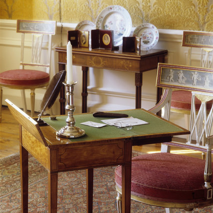 A close up of a writing desk and candle, to be found in the Drawing Room of Dyrham Park