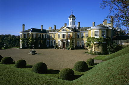 The east front of Polesden Lacey, showing the main range with projecting wings set against a blue sky