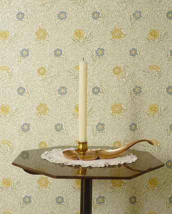 A candle in a candleholder against the William Morris