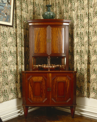 Mahogany corner cupboard designed by cousins Agnes and Rhoda Garrett and bought by the Beales for their London home in the 1870s, now in the Morning Room at Standen, West Sussex
