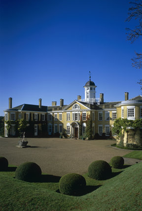 Polesden Lacey house, the beautiful east front with round  topiary bushes in foreground