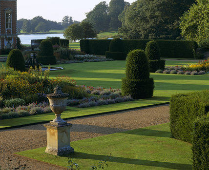 The Sunken Garden at Blickling Hall showing a stone ornament beside a gravel path, ribbon borders, hedges and a fountain with views of the parkland across the lake