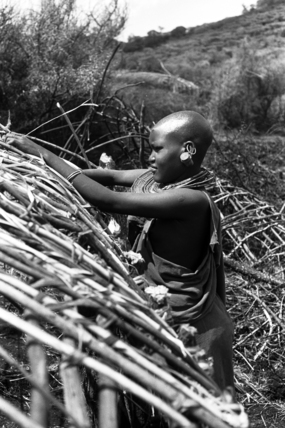 Maasai woman constructing a house