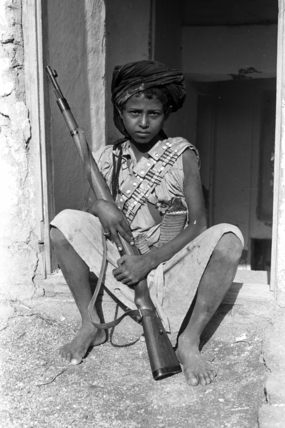 Udhr boy with a rifle