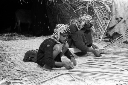 Suaid man and boy weaving mats