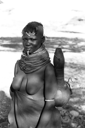Turkana woman carrying a water vessel