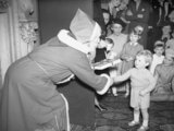 Father Christmas' presents Winston Churchill Jr., the Prime Minister's grandson, with a gift at a Christmas party at Admiralty House in London, 17 December 1942.